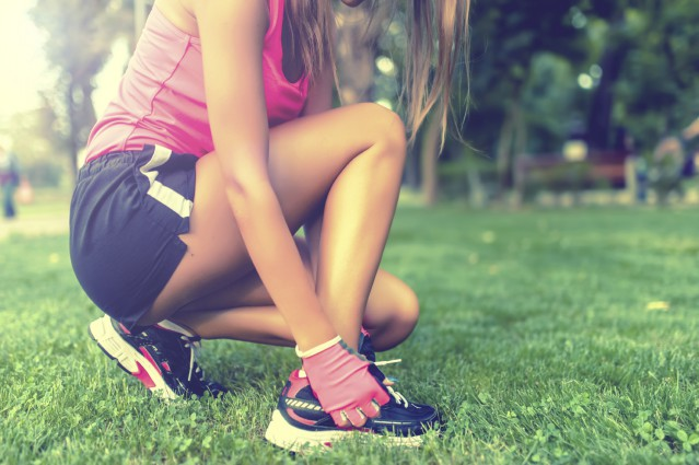 Close-up of active jogging female runner, preparing shoes for training and working out at fitness park