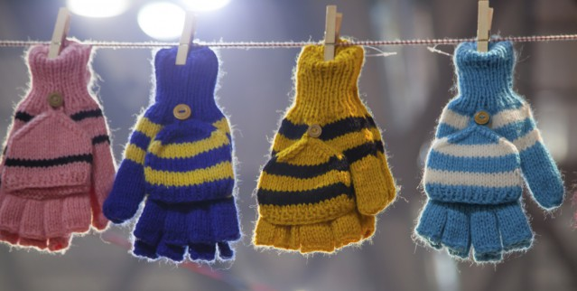Colorful gloves hanging by a thread