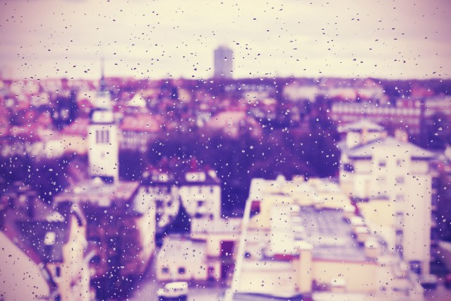 Purple abstract blurred urban background made of rain drops on window.